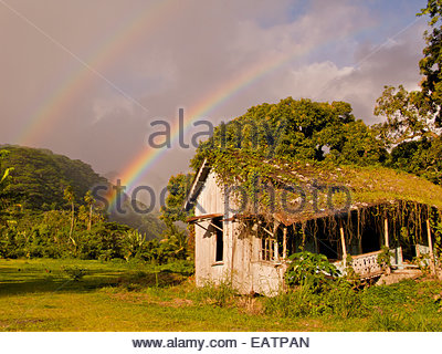 A double rainbow appears over an abandoned house in rural Tahiti. - Stock Photo