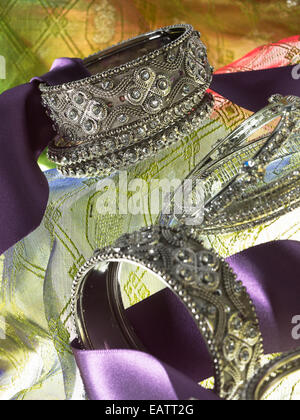 silver ornate bangle bracelets stacked with a decorative purple ribbon on a yellow green background - Stock Photo