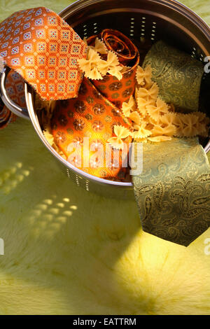 Bowtie Farfalle pasta  with mens ties in a colander - Stock Photo
