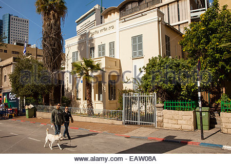 A couple and dog walk past Bauhaus Architecture in Tel Aviv. - Stock Photo