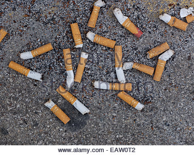 Cigarette butts litter the asphalt of a parking lot. - Stock Photo
