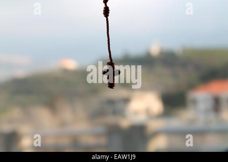 A hanging small knotted rosary with crucifix on a natural background.