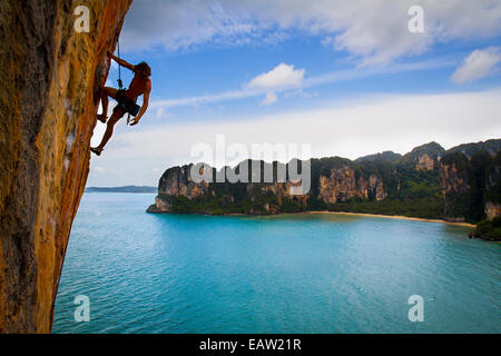 An austrian climber onsighs Orange Juice a sustained 7b+ (5.12c) over Railay Bay in Thailand 17th of September. - Stock Photo