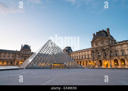 Courtyard and glass pyramid of the Louvre Museum at sunrise, Paris, Îsle-de-France, France - Stock Photo
