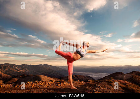 Senior woman doing yoga pose on top of mountain at sunset with landscape and desert valley below. - Stock Photo