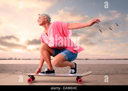 Youthful senior woman on skateboarding along beach at sunset, birds flying in the background. - Stock Photo