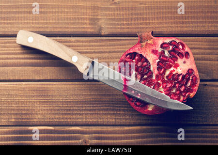 red pomegranate on wooden table - Stock Photo