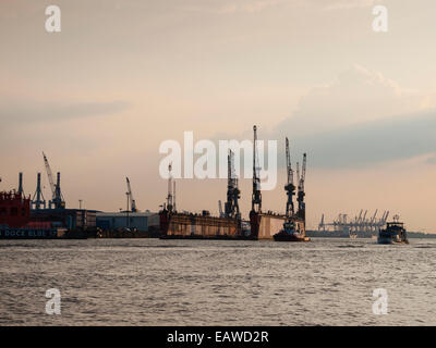 The sun is setting upon an empty dry dock of German shipbuilder 'Blohm+Voss' is floating on the Elbe river at Hamburg - Stock Photo