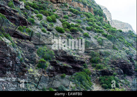 Wire mesh netting catches boulders that fall from a cliff onto a road. - Stock Photo