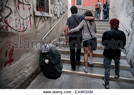 People passing a beggar sitting on steps leading to a bridge. - Stock Photo