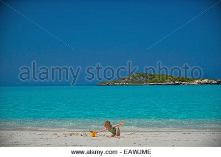 A young girl plays on Tropic of Cancer Beach on Little Exuma, Bahamas. - Stock Photo