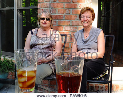 Two women friends enjoy the sun on a porch with glasses of iced tea. - Stock Photo