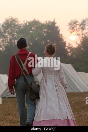 A young couple dressed in Civil War era clothing walk arm in arm. - Stock Photo