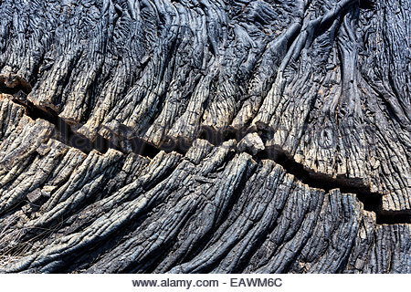 Deep crack in cooled ropelike pahoehoe lava flow. - Stock Photo