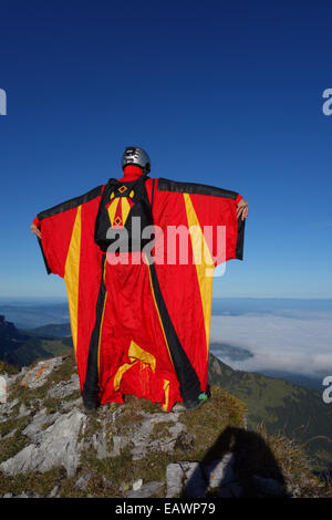 BASE jumper is exiting from a cliff down into the deep valley. Thereby he is within a wingsuit to fly fare away - Stock Photo