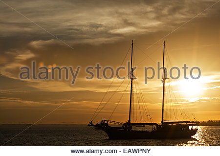 A sailing vessel at sunset in the Port of Sorong, Indonesia. - Stock Photo