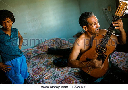 A shirtless man plays a guitar while sitting on his bed. - Stock Photo