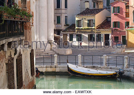 A boat in a small canal in the Cannaregio District of Venice. - Stock Photo