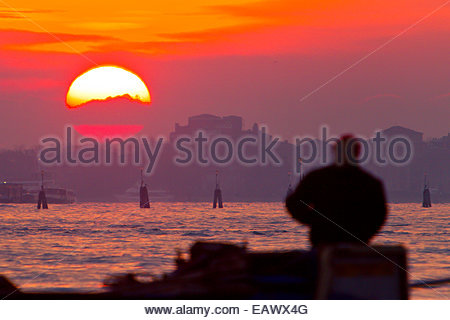 A man in silhouette watches the sunrise over the Grand Canal. - Stock Photo