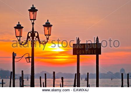 Sunrise over the gondola station at Saint Mark's Square in Venice. - Stock Photo