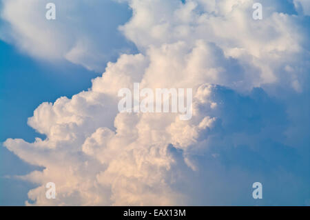 A billowing thunderhead storm forms over a tropical rainforest canopy. - Stock Photo