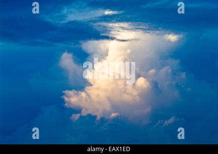 A menacing thunderhead storm forms over a tropical rainforest canopy after sunset. - Stock Photo