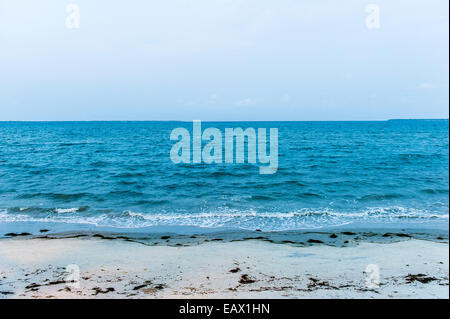 Tropical waves from the ocean lap the sandy shoreline of a bay after sunset. - Stock Photo