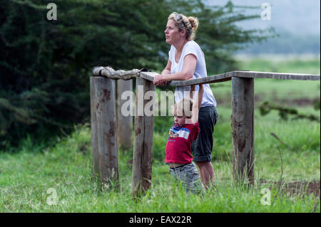 A bored boy swings on a fence rail whilst his mother watches hippos on safari. - Stock Photo