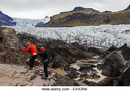 Tourists climbing up with aid of a rope, to hike on Vatnajokull glacier, Iceland's largest, and one of the largest - Stock Photo