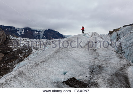 A tourist hiking on Vatnajokull glacier, Iceland's largest, and one of the largest in Europe. - Stock Photo