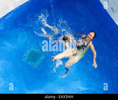 Mother and son swimming in a swimming pool - Stock Photo