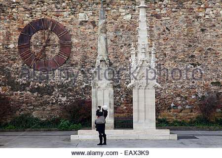 A woman photographs a clock on a medieval fortress wall near statues of church towers on Kaptol Square in Zagreb. - Stock Photo
