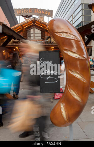 Witch House Large Oversize German Bratwurst with sign Christmas Markets and shoppers, Manchester, UK - Stock Photo