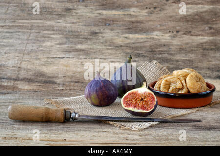 Fresh cut and dried figs with knife on wood and burlap - Stock Photo
