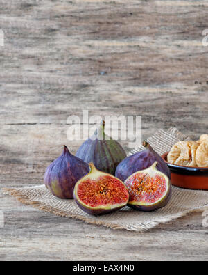 Fresh cut and dried figs on wood and burlap - Stock Photo