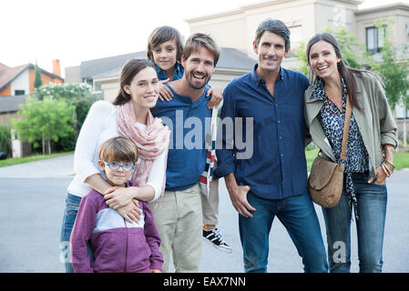 Family posing together on suburban street, portrait - Stock Photo