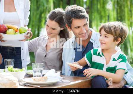 Family eating together outdoors, father holding son on lap - Stock Photo