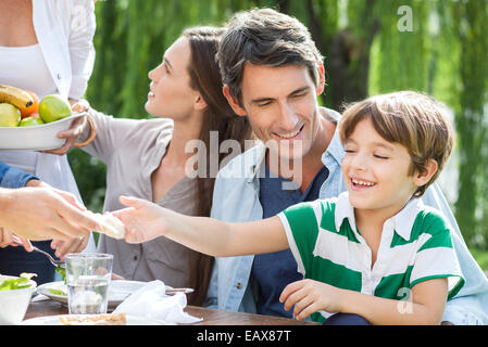 Family eating healthy meal together outdoors, father holding son on lap - Stock Photo