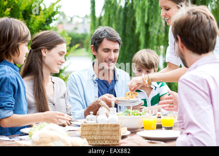 Family eating together at outdoor gathering - Stock Photo