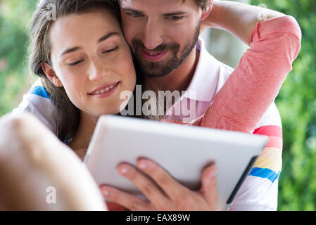 Young couple using digital tablet together outdoors - Stock Photo
