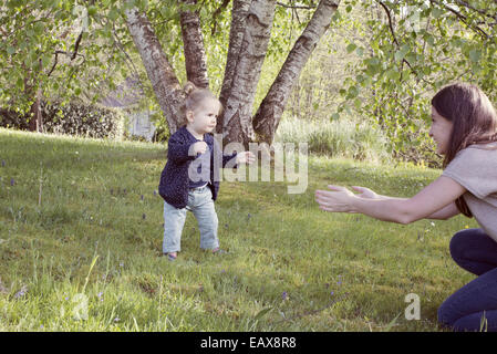 Baby girl taking her first steps outdoors - Stock Photo