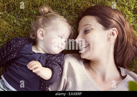 Mother and baby girl lying on grass, smiling at each other - Stock Photo