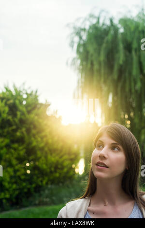 Young woman enjoying natural beauty of park - Stock Photo