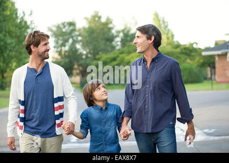 Fathers holding hands with son outdoors - Stock Photo