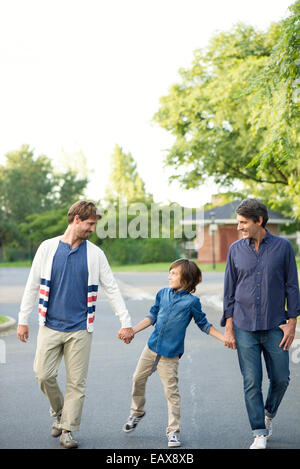 Boy walking with his fathers outdoors - Stock Photo