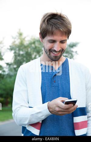 Man using smartphone outdoors - Stock Photo