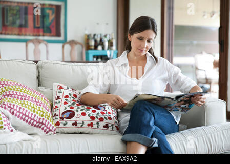 Woman sitting on sofa reading magazine - Stock Photo