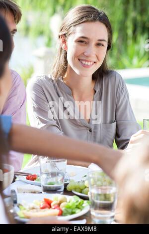 Young woman enjoying picnic outdoors - Stock Photo