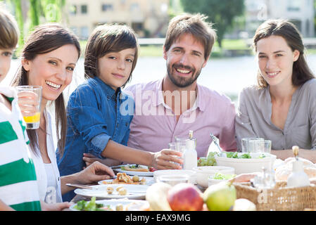 Family eating together outdoors, portrait - Stock Photo