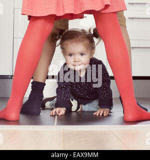 Baby girl crawling through siblings' legs - Stock Photo